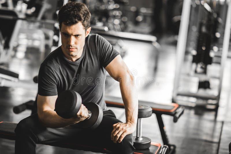 Κατάλληλος καυκάσιος όμορφος νεαρός άνδρας και μεγάλος μυς sportswear Αλτήρας εκμετάλλευσης νεαρών άνδρων κατά τη διάρκεια μιας κ στοκ εικόνα με δικαίωμα ελεύθερης χρήσης