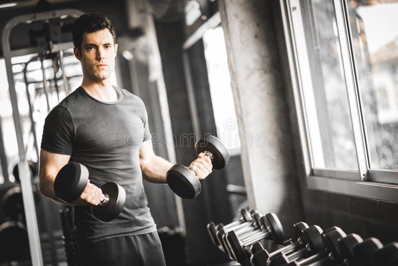 Κατάλληλος καυκάσιος όμορφος νεαρός άνδρας και μεγάλος μυς sportswear Αλτήρας εκμετάλλευσης νεαρών άνδρων κατά τη διάρκεια μιας κ στοκ εικόνες