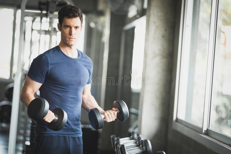 Κατάλληλος καυκάσιος όμορφος νεαρός άνδρας και μεγάλος μυς sportswear Αλτήρας εκμετάλλευσης νεαρών άνδρων κατά τη διάρκεια μιας κ στοκ φωτογραφία με δικαίωμα ελεύθερης χρήσης