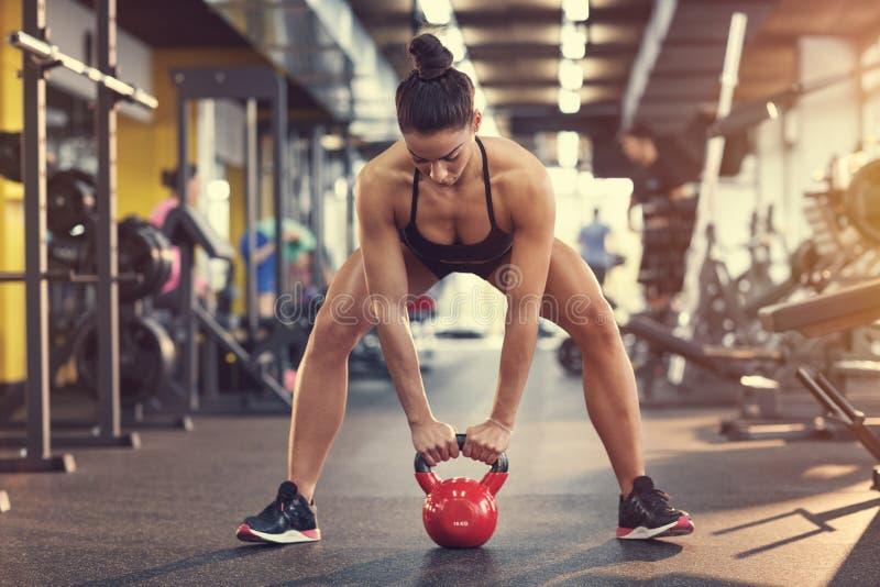 Κατάλληλο κορίτσι στην άσκηση γυμναστικής που χρησιμοποιεί το βάρος κουδουνιών κατσαρολών στοκ εικόνες