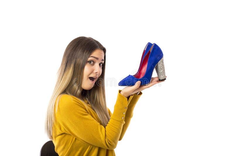 Κατάπληκτη νέα γυναίκα που κρατά ένα ζευγάρι των υψηλών παπουτσιών τακουνιών πέρα από το άσπρο υπόβαθρο στοκ εικόνα