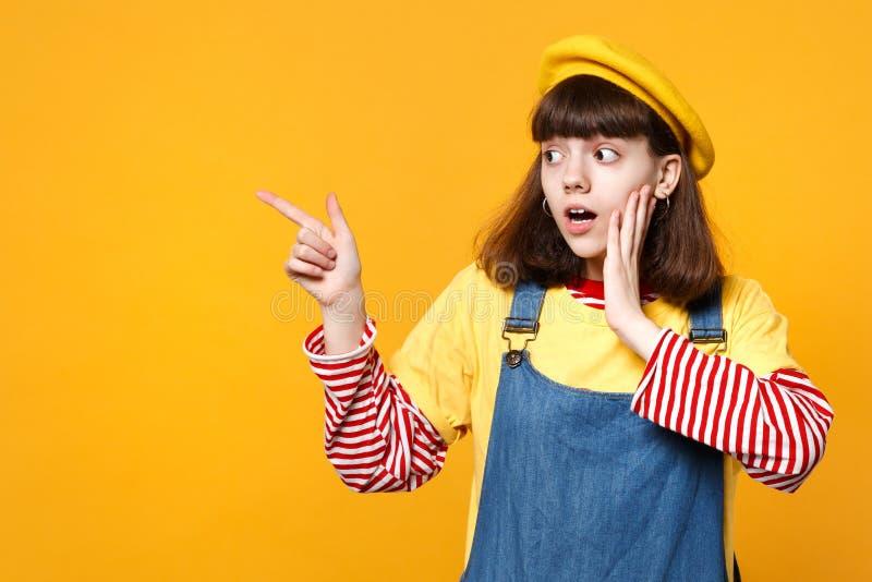 Κατάπληκτος έφηβος κοριτσιών γαλλικό beret, τζιν sundress που βάζει το χέρι στο μάγουλο, που δείχνει το αντίχειρα που απομονώνετα στοκ φωτογραφίες
