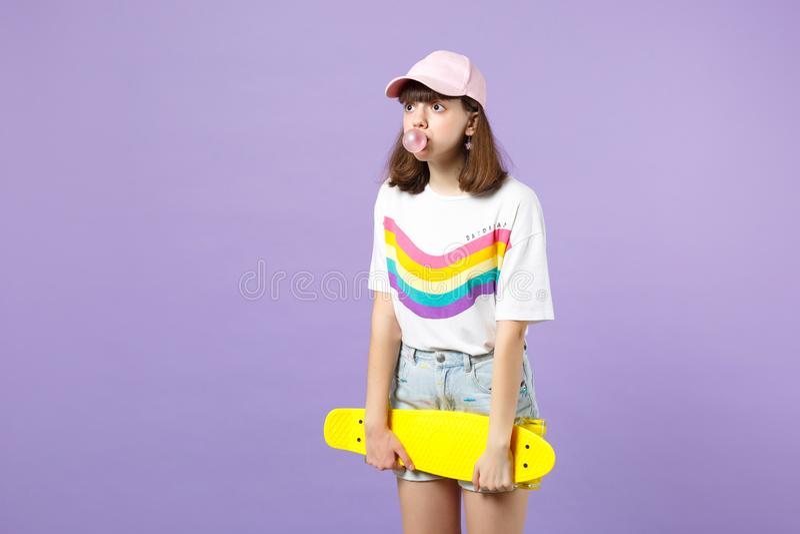 Κατάπληκτο κορίτσι εφήβων στα ζωηρά ενδύματα που φυσούν τη γόμμα φυσαλίδων, που κρατά κίτρινο skateboard κατά μέρος απομονωμένος  στοκ φωτογραφία με δικαίωμα ελεύθερης χρήσης