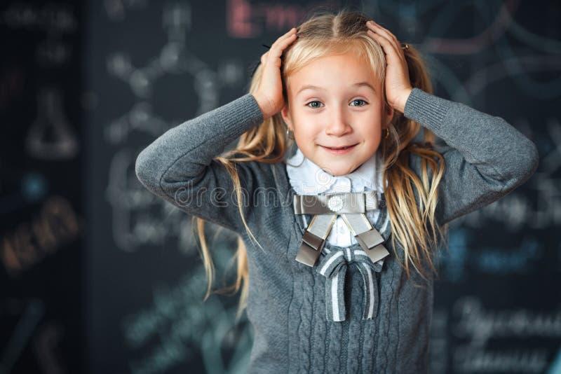 Κατάπληκτο παιδί σχολείου που μαθαίνει Math, τύποι μαθηματικών κιμωλίας στον πίνακα, έκπληκτο παιδί κοριτσιών με το βιβλίο πέρα α στοκ φωτογραφία