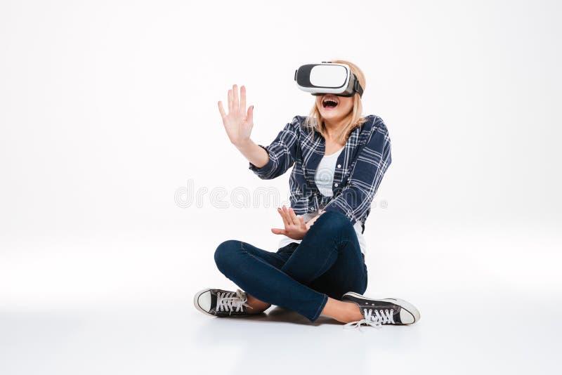 Κατάπληκτη συνεδρίαση γυναικών στο πάτωμα που φορά τα γυαλιά VR στοκ εικόνα με δικαίωμα ελεύθερης χρήσης