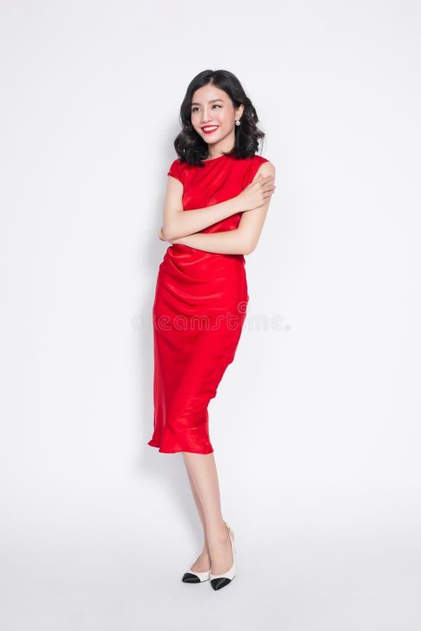 Κατάπληξη της ασιατικής γυναίκας πολυτέλειας στο μοντέρνο κόκκινο φόρεμα κομμάτων στοκ φωτογραφία