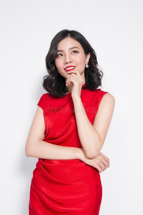 Κατάπληξη της ασιατικής γυναίκας πολυτέλειας στο μοντέρνο κόκκινο φόρεμα κομμάτων στοκ εικόνα