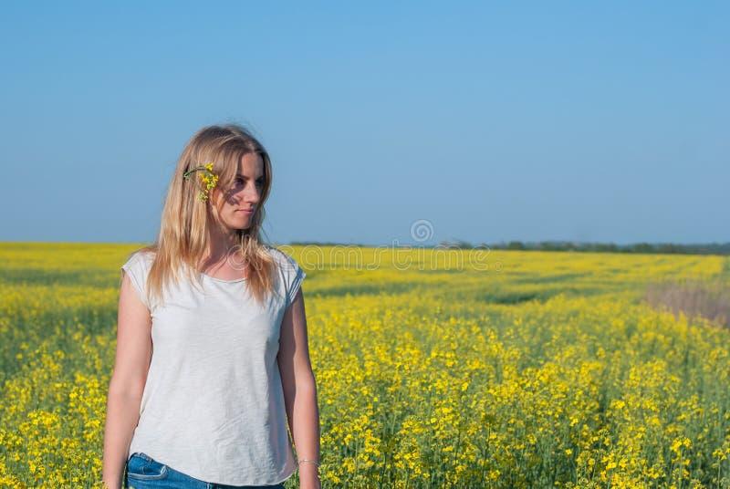 Κατάπληξη του ρομαντικού κοριτσιού σε έναν τομέα των κίτρινων λουλουδιών στοκ φωτογραφίες