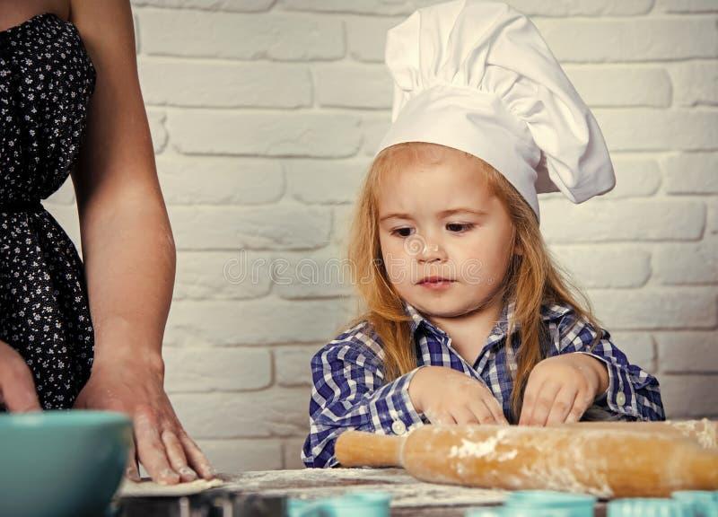 Κατάρτιση μαγειρέματος Μάγειρας παιδιών στο καπέλο αρχιμαγείρων που βοηθά τη μητέρα στοκ εικόνες