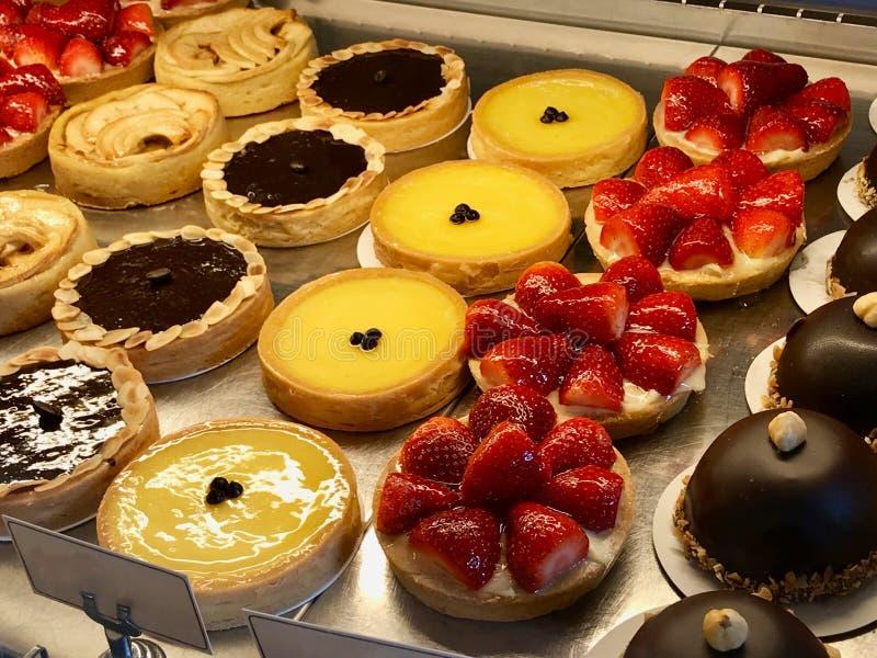 Κατάστημα ζύμης με την ποικιλία tarts, κέικ, creme brulle, με τη φράουλα, τη σοκολάτα, το λεμόνι, τα αχλάδια και τις φέτες μήλων  στοκ φωτογραφία
