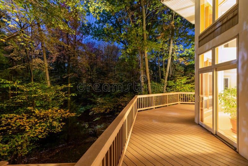Κατάστρωμα στο σπίτι στο δάσος τη νύχτα στοκ φωτογραφίες