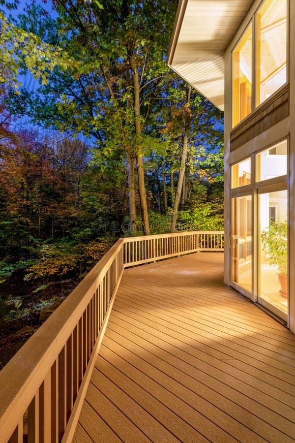 Κατάστρωμα στο σπίτι στο δάσος τη νύχτα στοκ εικόνα