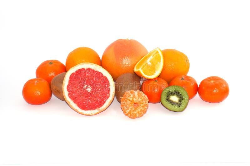 Κατάταξη ολόκληρων και των τεμαχισμένων εξωτικών φρούτων σε ένα άσπρο υπόβαθρο Πορτοκαλιές φέτες ακτινίδιων και κινεζικής γλώσσας στοκ εικόνα