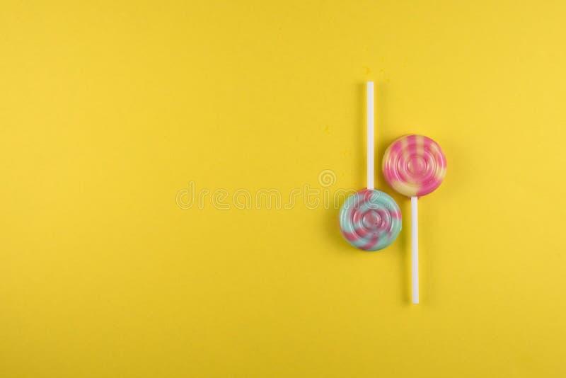Κατάταξη του ζωηρόχρωμου lollipop πέρα από το κίτρινο χρωματισμένο υπόβαθρο στοκ εικόνες