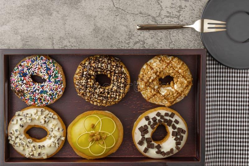 Κατάταξη των donuts στον ξύλινο δίσκο με το δίκρανο πετσετών και το μικρό πιάτο στοκ εικόνες