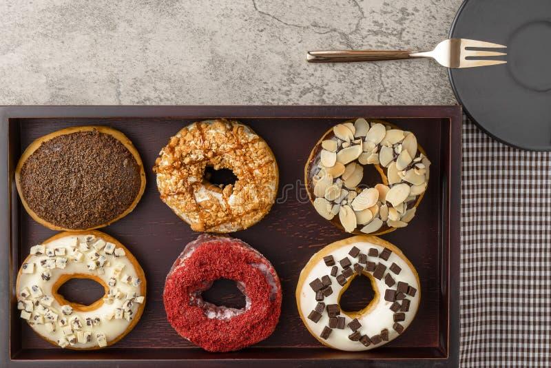 Κατάταξη των donuts στον ξύλινο δίσκο με το σκοτεινό πιάτο και το μικρές δίκρανο και την πετσέτα στοκ φωτογραφίες