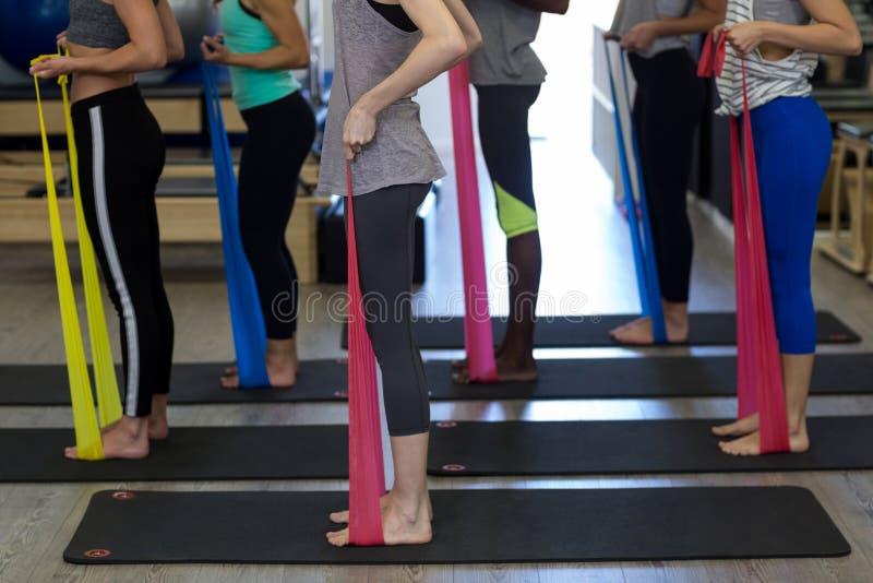 Κατάλληλες γυναίκες που εκτελούν την τεντώνοντας άσκηση με τη ζώνη αντίστασης στοκ εικόνες με δικαίωμα ελεύθερης χρήσης