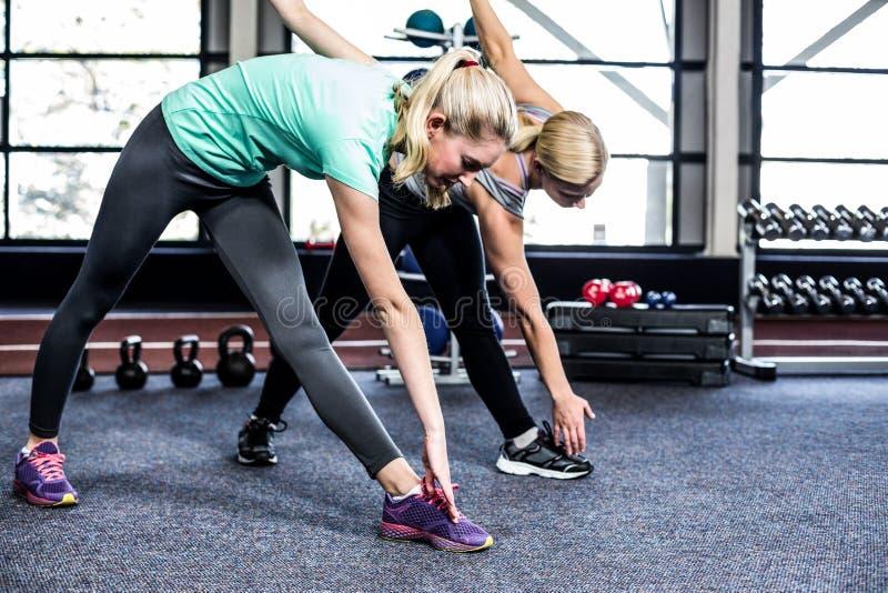 Κατάλληλες γυναίκες που τεντώνουν στη γυμναστική στοκ εικόνα