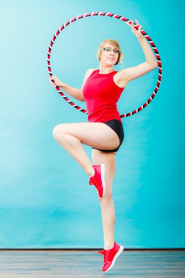 Κατάλληλη γυναίκα με τη στεφάνη hula που κάνει την άσκηση στοκ φωτογραφίες
