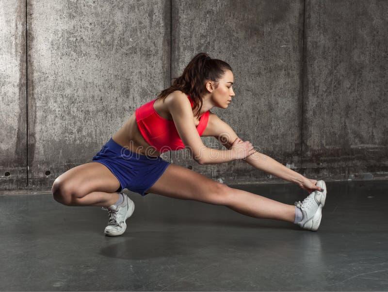 Κατάλληλη γυναίκα που τεντώνει το πόδι της που θερμαίνει στοκ εικόνα