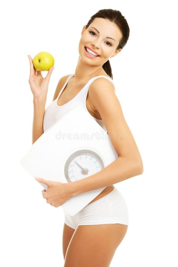 Κατάλληλη γυναίκα πλάγιας όψης με ένα μήλο και ένα βάρος στοκ φωτογραφία με δικαίωμα ελεύθερης χρήσης