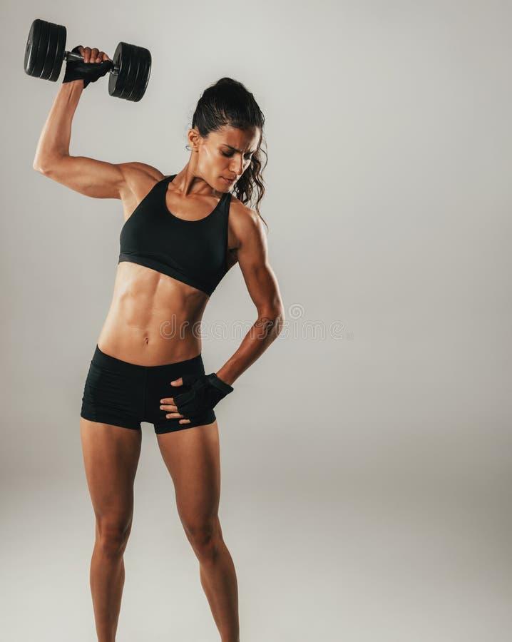 Κατάλληλη ισχυρή νέα γυναίκα με ένα τονισμένο μυϊκό σώμα στοκ εικόνες
