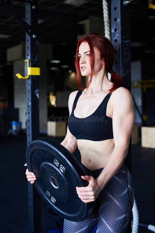 Κατάλληλη νέα γυναίκα που επιλύει σε μια γυμναστική, που φαίνεται στοκ εικόνα
