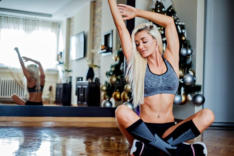 Κατάλληλη νέα γυναίκα που κάνει την τεντώνοντας άσκηση στο καθιστικό στοκ φωτογραφία με δικαίωμα ελεύθερης χρήσης