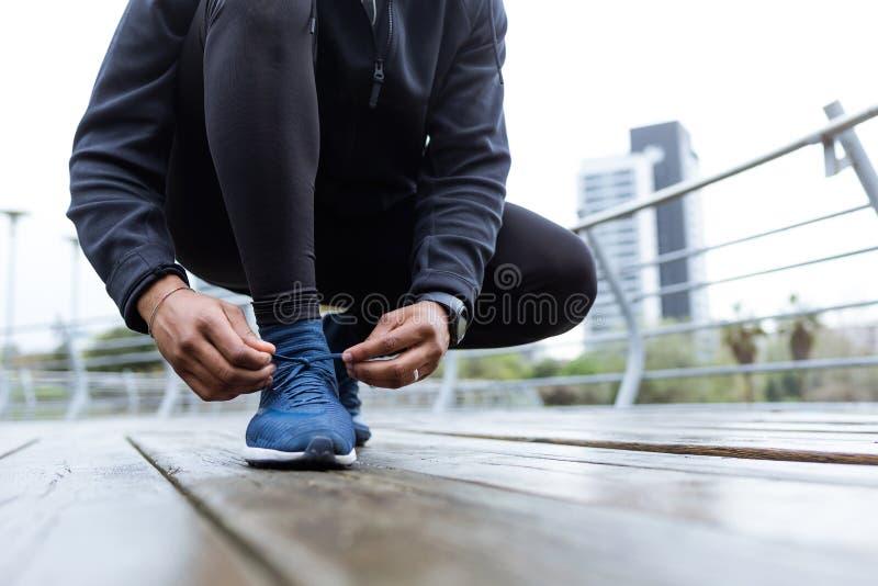 Κατάλληλος και φίλαθλος νεαρός άνδρας που δένει τις δαντέλλες της πριν από ένα τρέξιμο cit στοκ εικόνα