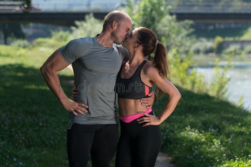Κατάλληλο ζεύγος που φιλά μεταξύ τους που στηρίζεται μετά από να τρέξει στοκ φωτογραφία με δικαίωμα ελεύθερης χρήσης