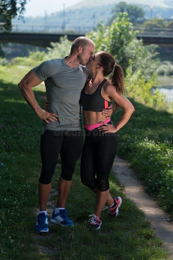 Κατάλληλο ζεύγος που φιλά μεταξύ τους που στηρίζεται μετά από να τρέξει στοκ φωτογραφίες