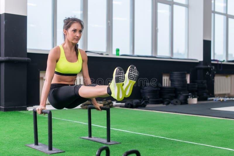 Κατάλληλο ισχυρό να κάνει γυναικών λ-κάθεται επιλύει στη γυμναστική, ανυψωτικός επάνω τα πόδια της, χρησιμοποιώντας τους παράλληλ στοκ εικόνα