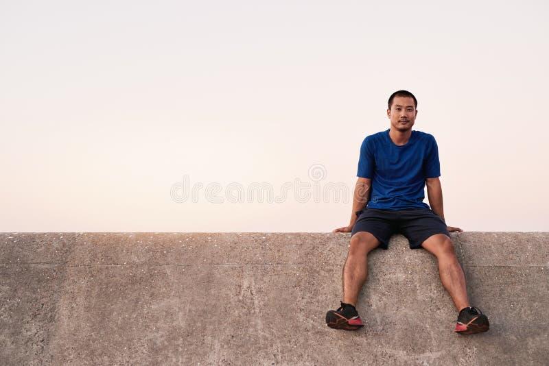 Κατάλληλο νέο ασιατικό άτομο που παίρνει ένα σπάσιμο από ένα τρέξιμο στοκ φωτογραφίες με δικαίωμα ελεύθερης χρήσης