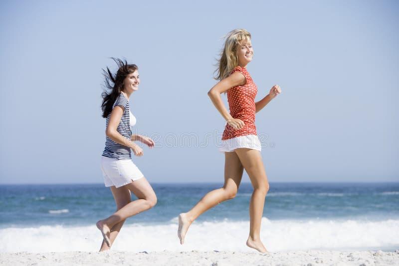κατά μήκος της παραλίας που τρέχει δύο γυναίκες στοκ φωτογραφίες