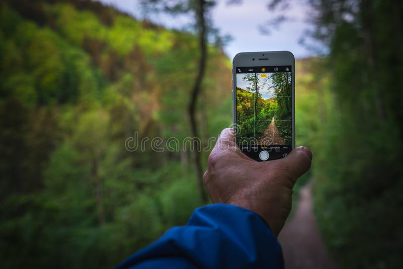 Κατά την πεζοπορία, πάρτε τις εικόνες με το κινητό τηλέφωνό σας στοκ φωτογραφίες