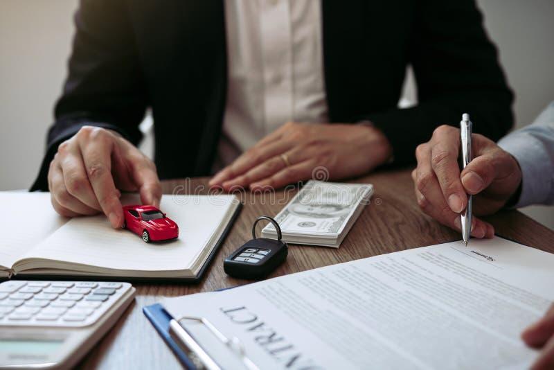 Κατά την υπογραφή της σύμβασης, ο πωλητής αυτοκινήτων παρέδωσε το αυτοκίνητο του μοντέλου παιχνιδιών στον νέο αγοραστή αυτοκινήτω στοκ εικόνες