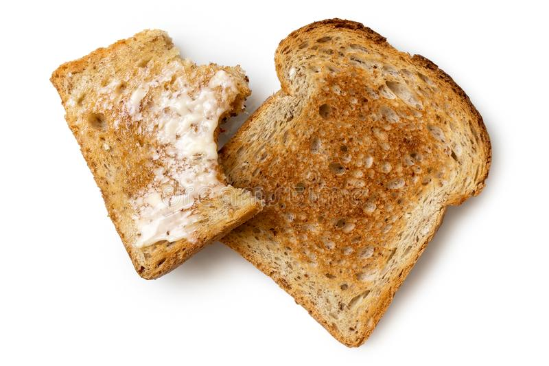 Κατά το ήμισυφαγωμένη ?αγωμένη βουτυρωμένη φέτα ολόκληρης της φρυγανιάς σίτου και ολόκληρου του ξηρού sli στοκ εικόνα
