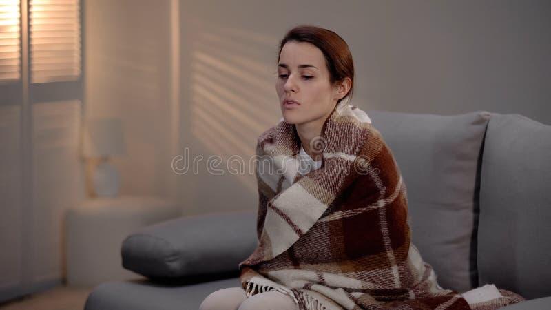 Κατά το τέλος άρρωστη καταθλιπτική νέα κυρία που καλύπτεται με τη συνεδρίαση καρό μόνο στο άσυλο στοκ εικόνες με δικαίωμα ελεύθερης χρήσης