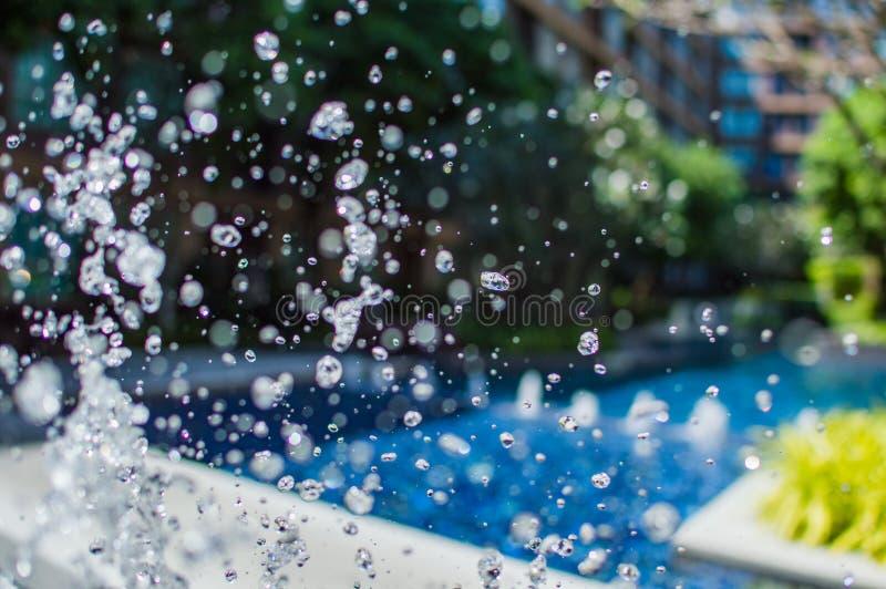 Καταβρέχοντας σταγονίδια παγώματος του νερού στον αέρα κοντά στην πισίνα στοκ φωτογραφία