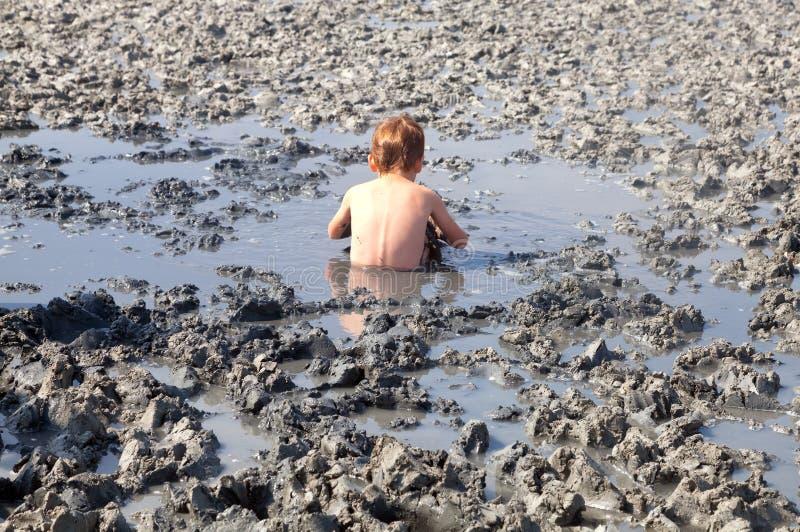 Καταθέσεις του φυσικού αργίλου θεραπείας Το παιδί δέχεται πρόθυμα τη λάσπη β στοκ φωτογραφίες