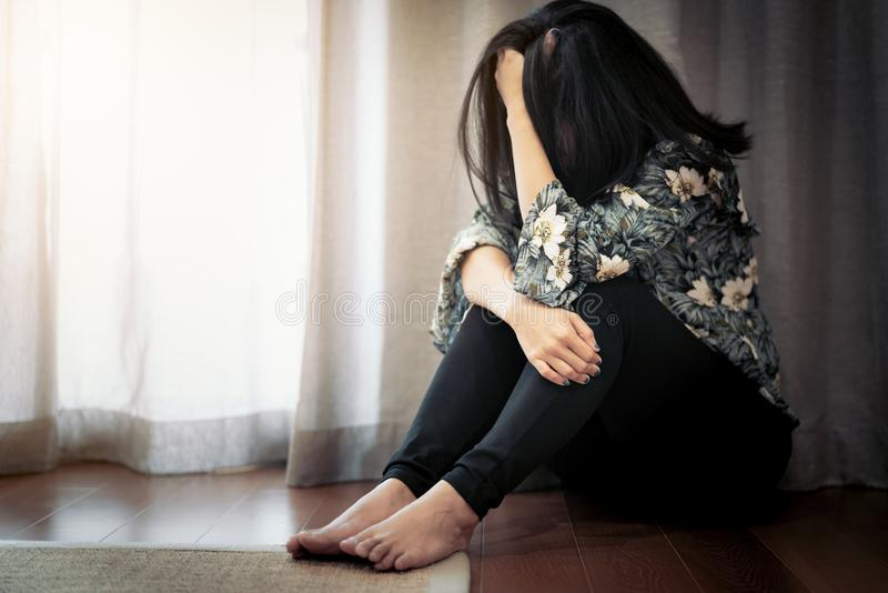Καταθλιπτικές γυναίκες που κάθονται κοντά στην κουρτίνα στο καθιστικό, μόνο, θλίψη, συναισθηματική έννοια στοκ φωτογραφίες