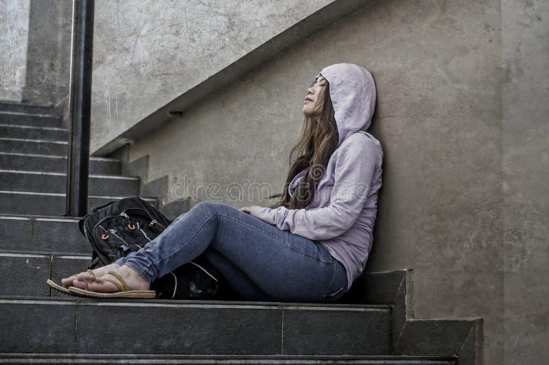Καταθλιπτική ασιατική ιαπωνική γυναίκα σπουδαστών ή φοβερισμένη συνεδρίαση κοριτσιών εφήβων υπαίθρια στο θύμα σκαλών οδών του αισ στοκ φωτογραφίες