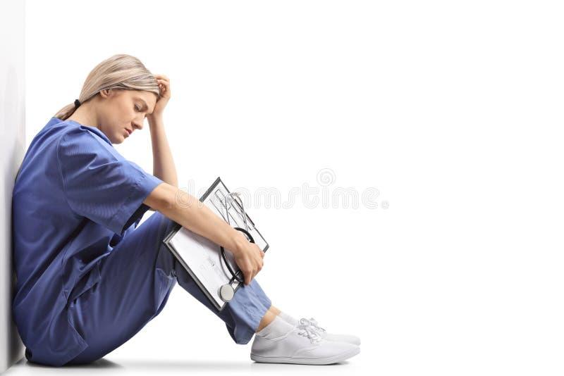 Καταθλιπτική θηλυκή συνεδρίαση γιατρών στο έδαφος και κλίση agains στοκ φωτογραφία με δικαίωμα ελεύθερης χρήσης