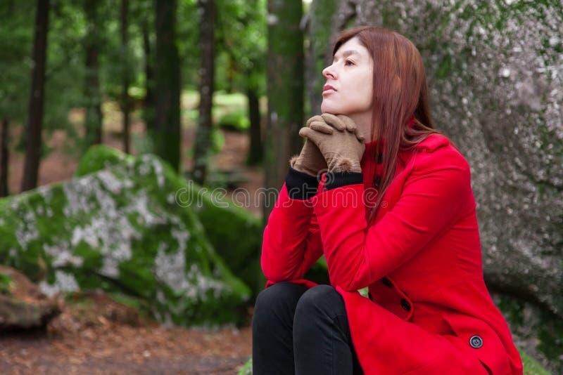 Καταθλιπτική και λυπημένη νέα γυναίκα που αισθάνεται τη συνεδρίαση κατάθλιψης στο δάσος, που ανατρέχει με τη μελαγχολική σκέψη στοκ φωτογραφία με δικαίωμα ελεύθερης χρήσης