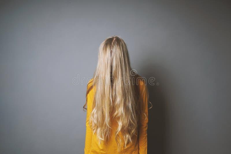 Καταθλιπτική νέα γυναίκα που κρύβει το πρόσωπό της πίσω από τα μακριά ξανθά μαλλιά στοκ εικόνα με δικαίωμα ελεύθερης χρήσης