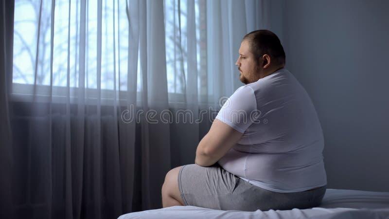 Καταθλιπτική παχιά συνεδρίαση ατόμων στο κρεβάτι στο σπίτι, που ανησυχείται για το υπερβολικό βάρος, αβεβαιότητες στοκ φωτογραφία με δικαίωμα ελεύθερης χρήσης