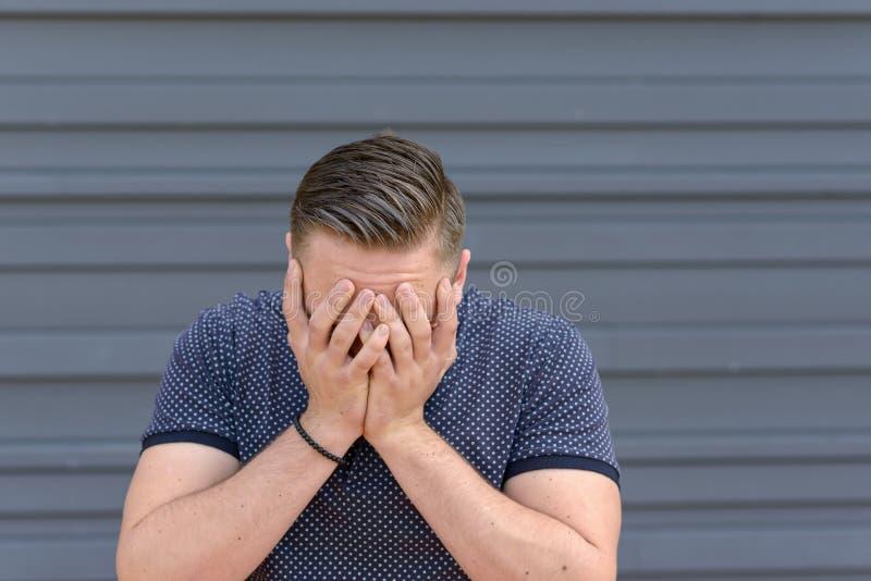 Καταθλιπτικός νεαρός άνδρας με το κεφάλι του στα χέρια του στοκ φωτογραφίες