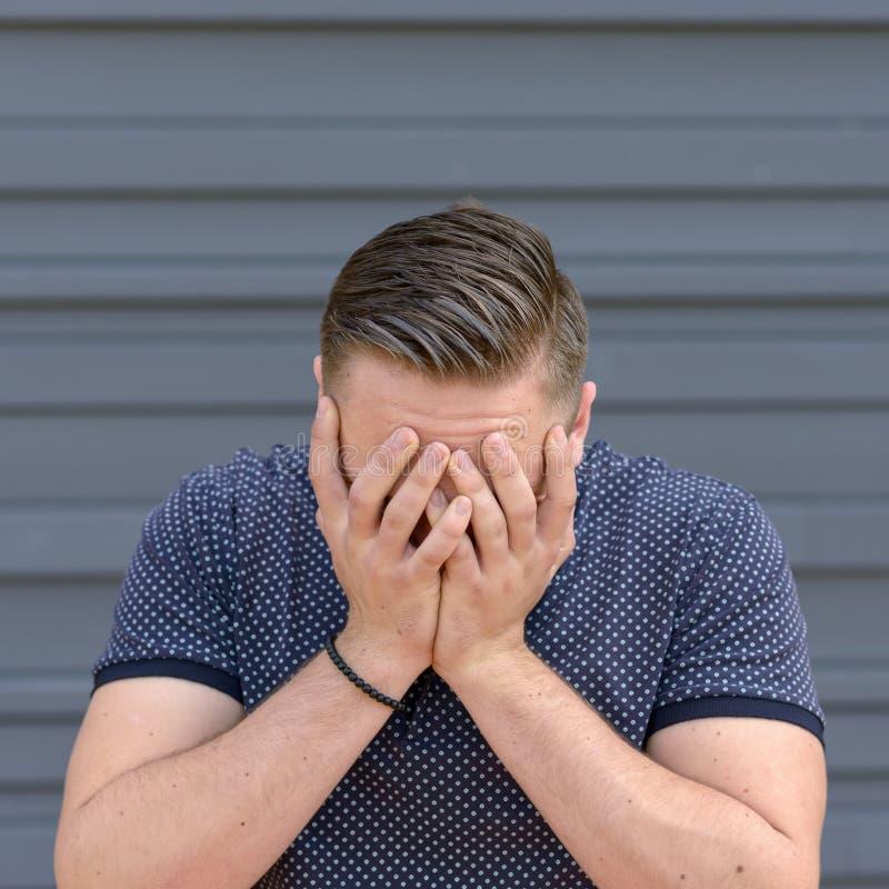 Καταθλιπτικός νεαρός άνδρας με το κεφάλι του στα χέρια του στοκ φωτογραφία