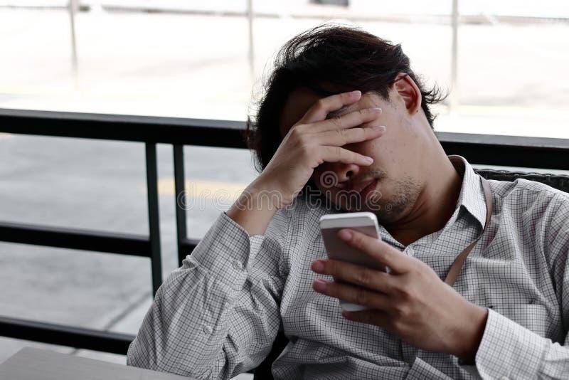 Καταθλιπτικό ασιατικό επιχειρησιακό άτομο με τα χέρια στο μέτωπο που εξετάζει κινητό έξυπνο τηλέφωνο στα χέρια του το γραφείο στοκ φωτογραφίες με δικαίωμα ελεύθερης χρήσης