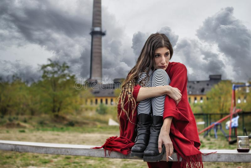 Καταθλιπτικό κορίτσι σε μια κόκκινη poncho συνεδρίαση σε έναν πάγκο μόνο στοκ εικόνα με δικαίωμα ελεύθερης χρήσης
